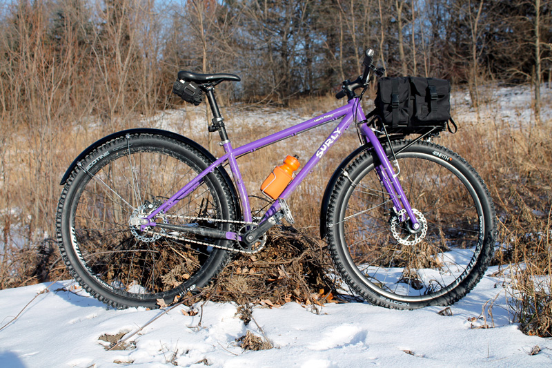 Right profile of a Surly Karate Monkey bike with fenders, 8 Pack rack with gear pack on top, on a snowy field with brush