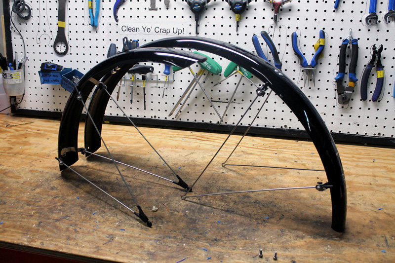 Side view of a black front and back fenders, with mounts, on top of a workbench with tool loaded pegboard behind