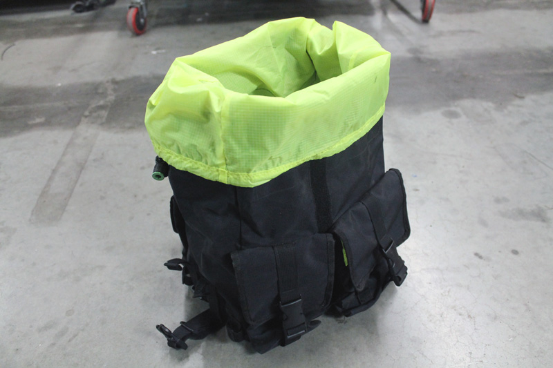 A Surly Petite Porteur House bag, black outside and lime green inside, set on a concrete floor