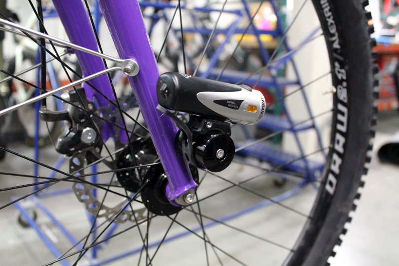 Right side view of the bottom half a purple bike fork with a light mounted and a wheel