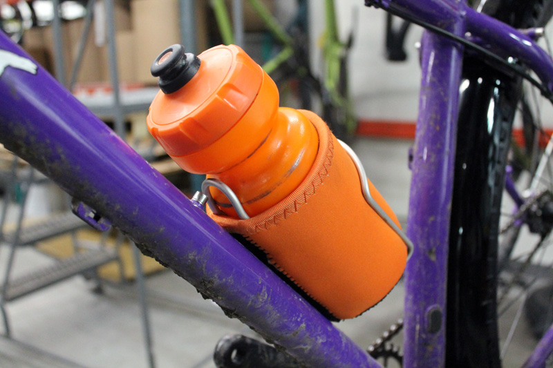 Close up view of a orange bottle inside a bottle cage, mounted to the down tube of a Surly Karate Monkey bike, purple