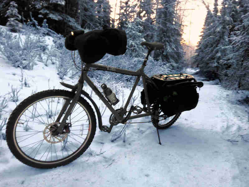 Left side view of an olive colored Surly Big Dummy bike with a front pack, parked on a snow covered trail in the forest