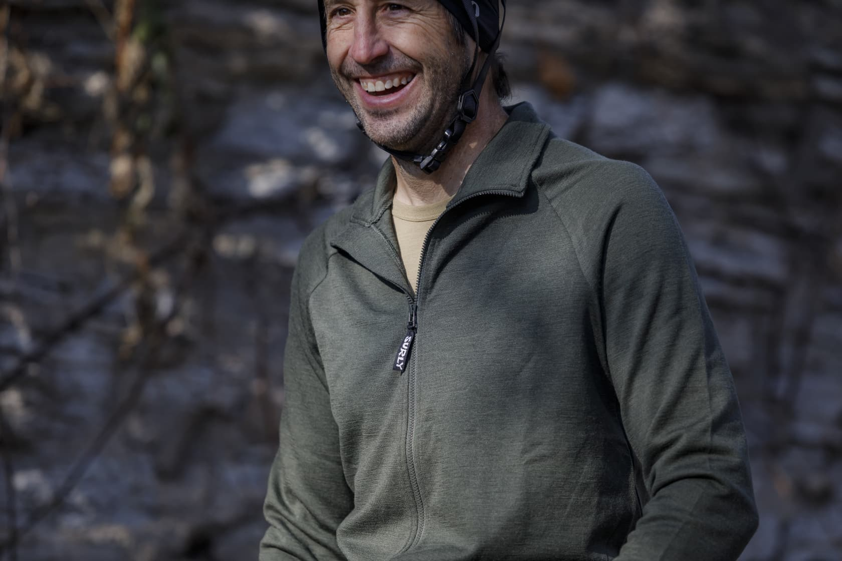 Person wearing a Surly long sleeve bike jersey, olive drab, and helmet in a blurry outdoor woods setting in background