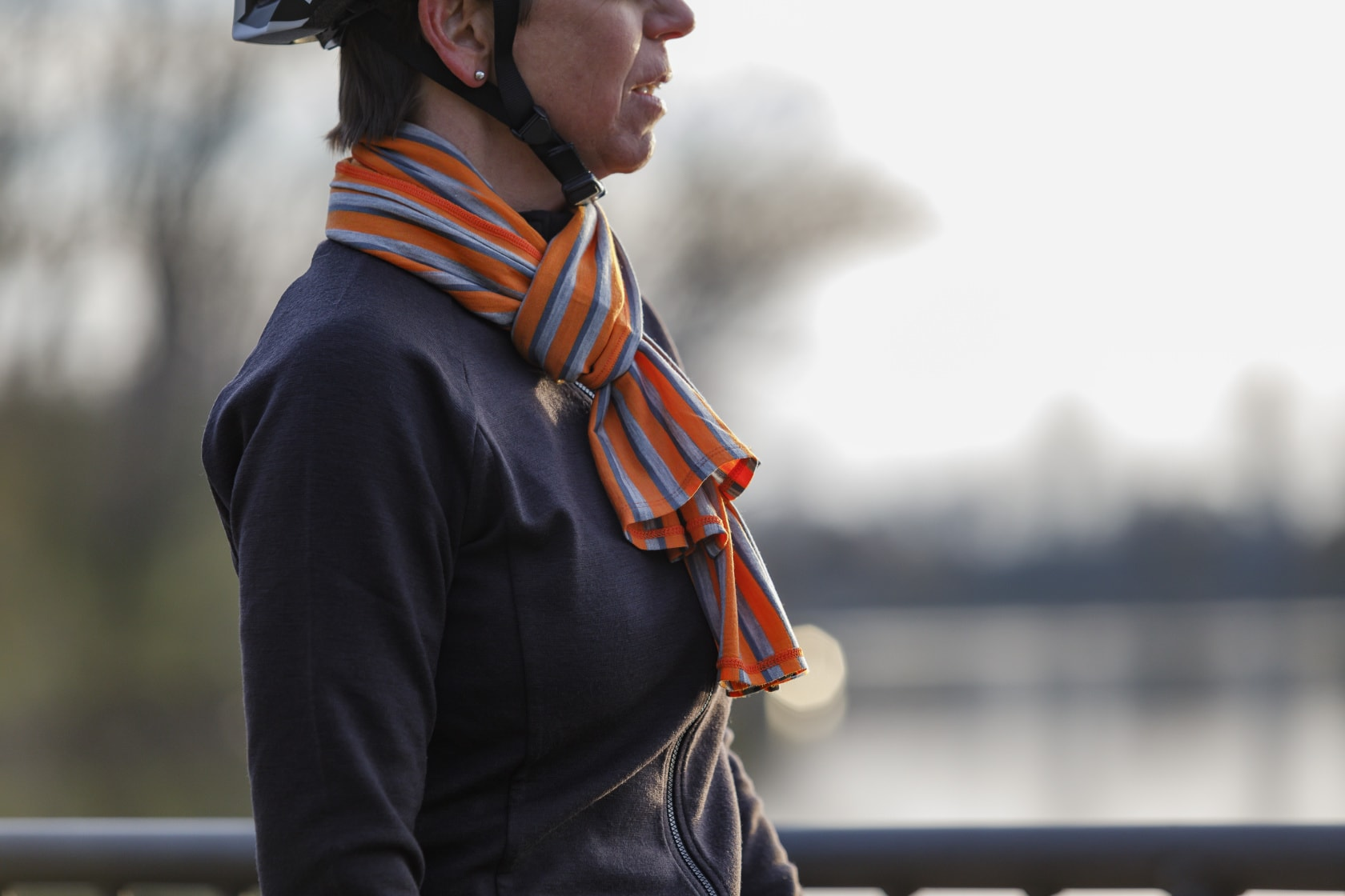 Right profile view of a person wearing a Surly Wool Scarf - Orange, Light Gray and blue parallel stripes