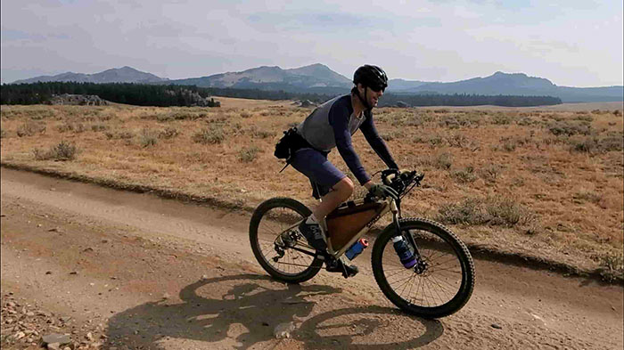 Person riding gold Surly Karate Monkey with Corner Bar on desert gravel road with mountains in background