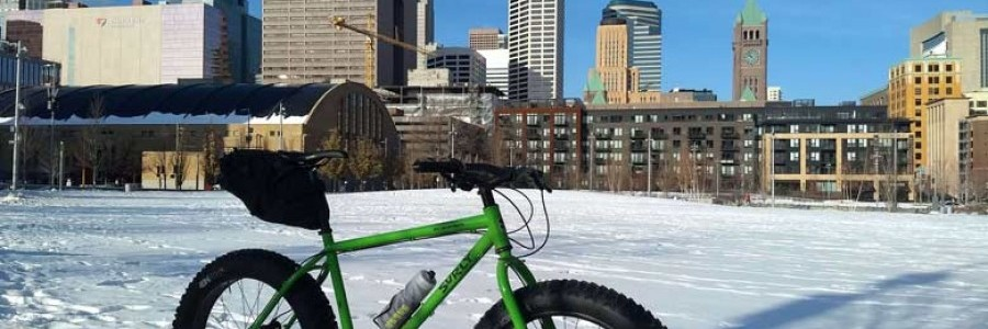 Surly Ice Cream Truck bike, green, with seat pack and water bottle, in snowy field with buildings in background