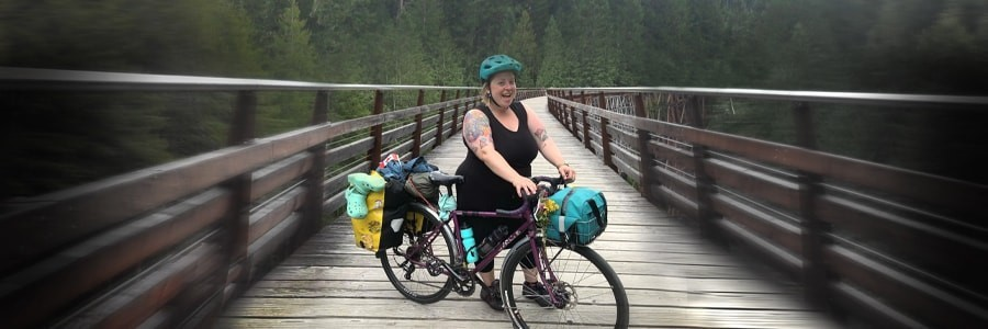 Cyclist stands on left side of fully geared Surly Straggler bike on wood bridge trail with pine trees in background