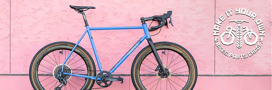 Surly Midnight Special Bike with Perry Winkle's Sparkle color on a sidewalk leaning on a pink stucco wall