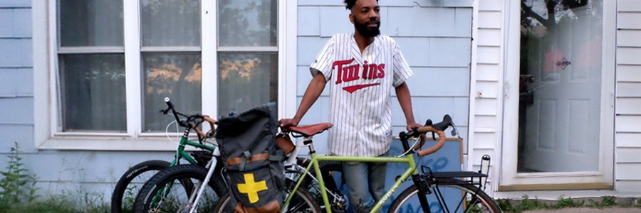Wesley stands in front of house wearing Twins jersey with lime color Surly bike in front of him and 2 bikes behind him