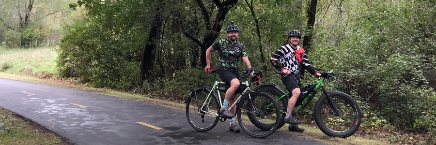 Two cyclists stand on a paved trail with their Surly bikes at a right profile view, green leafed trees in woods behind