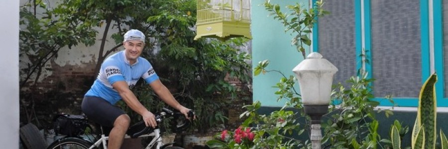 Cyclist sitting a white Surly Midnight Special bike with a seat pack poses in front of a home with plants and shrubbery