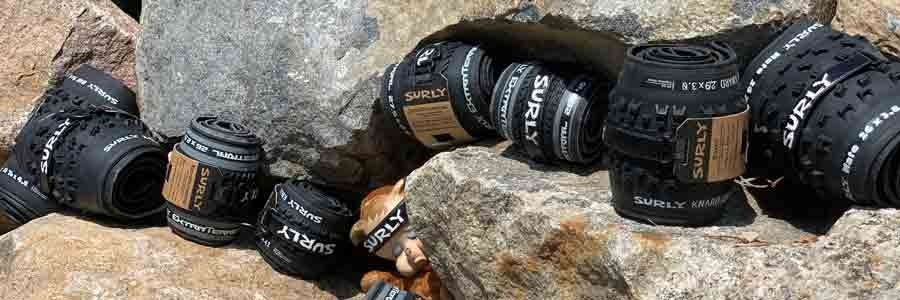 Black Surly bike tires in rolls between boulders and with a stuffed animal doll with a plastic wearing a Surly headband