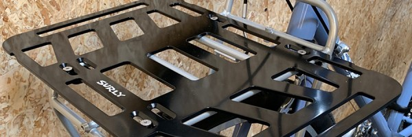 Surly TV Tray front rack, black, mounted to a Surly bike in front of an OSB wood wall