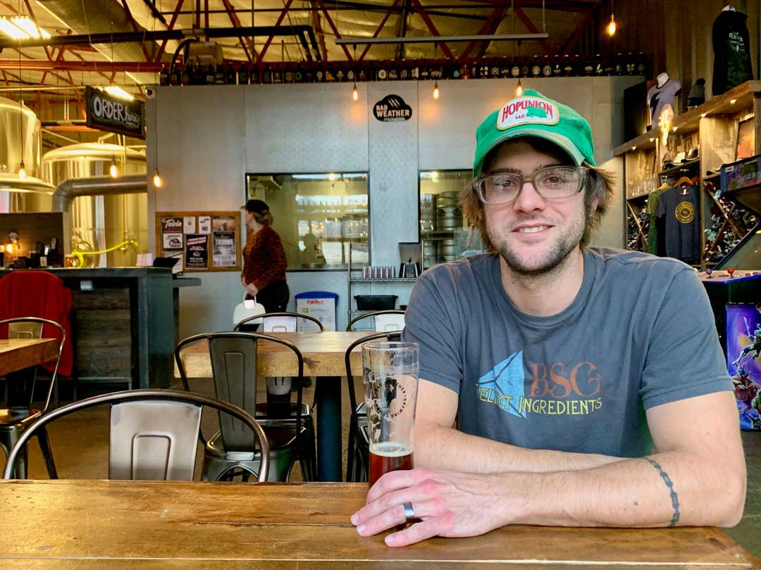 Head Brewer, Andy, wearing a green baseball cap and glasses sits at a table with a glass of beer at a brewery