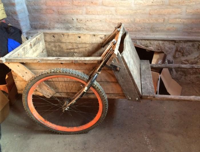 A custom made wheelbarrow against a stone wall