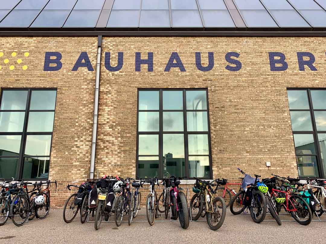 Cluster of bikes loaded with gear in front of three large windows on a brick Bauhaus Brewery building with glass roof