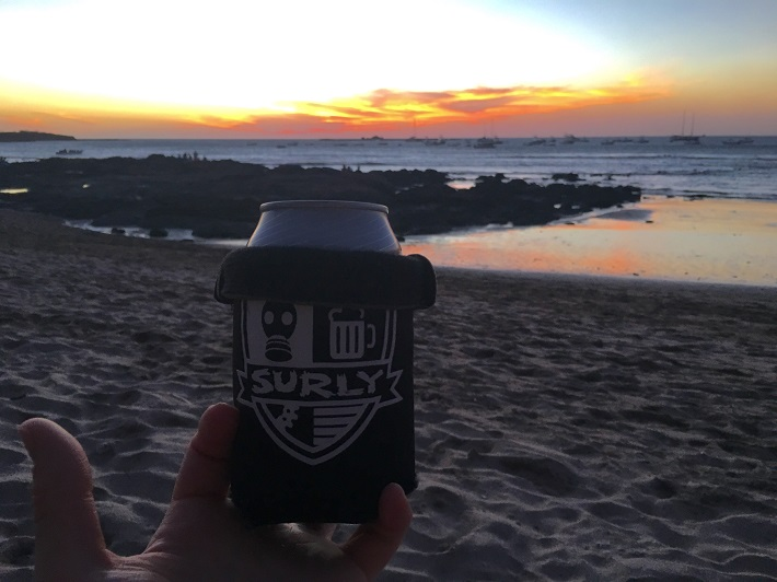 A hand holding up a Surly can cooler with a beach, the ocean and golden clouds above at dusk