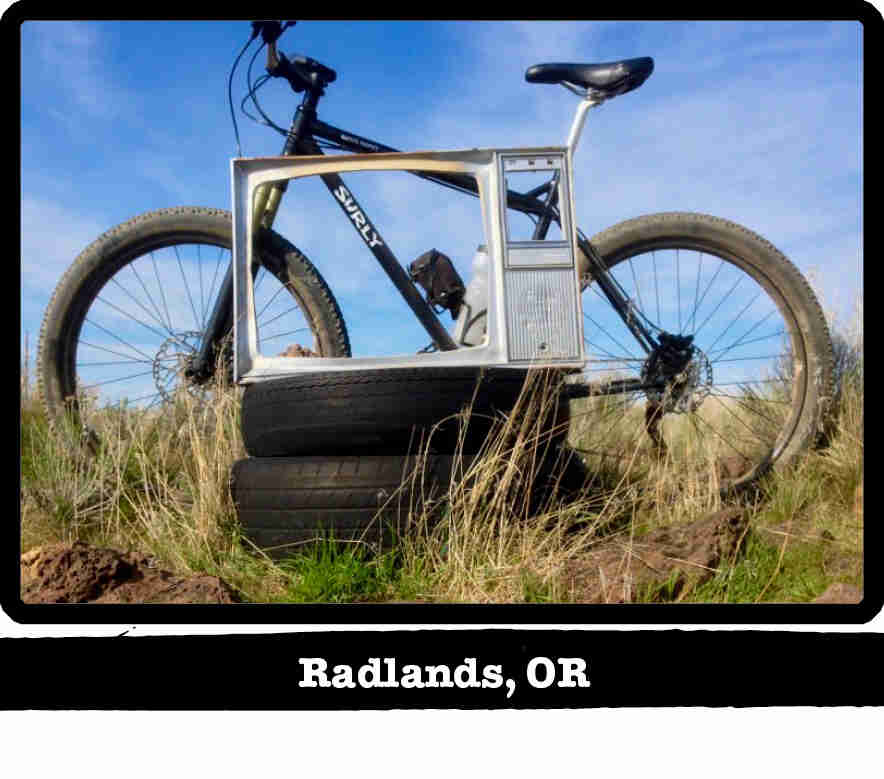 Left side view of a Surly Karate Monkey bike, black, in front of a TV frame on tires - Radlands, OR tag below image