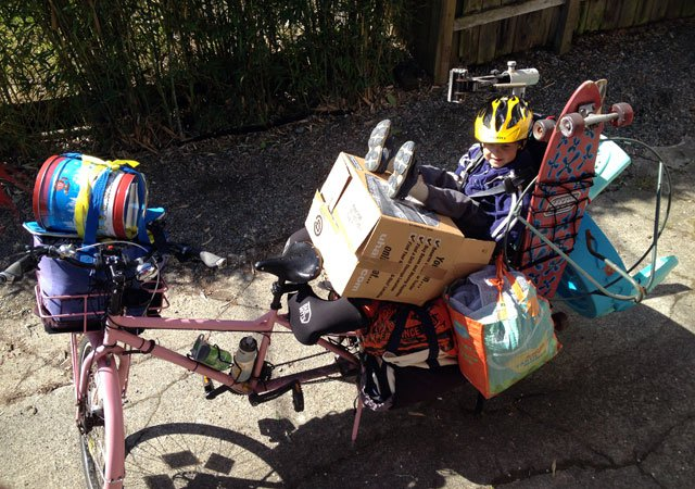 Downward, left side view of a pink Surly Big Dummy bike, loaded up, and a child sitting on a cardboard box, in the back