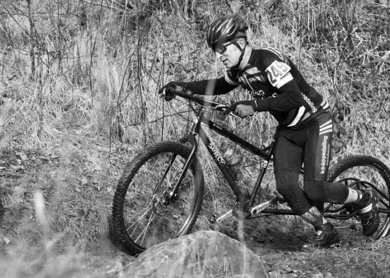 Left side view of a Surly Big Dummy bike, with a race cyclist pushing it up a dirt trail - black & white image