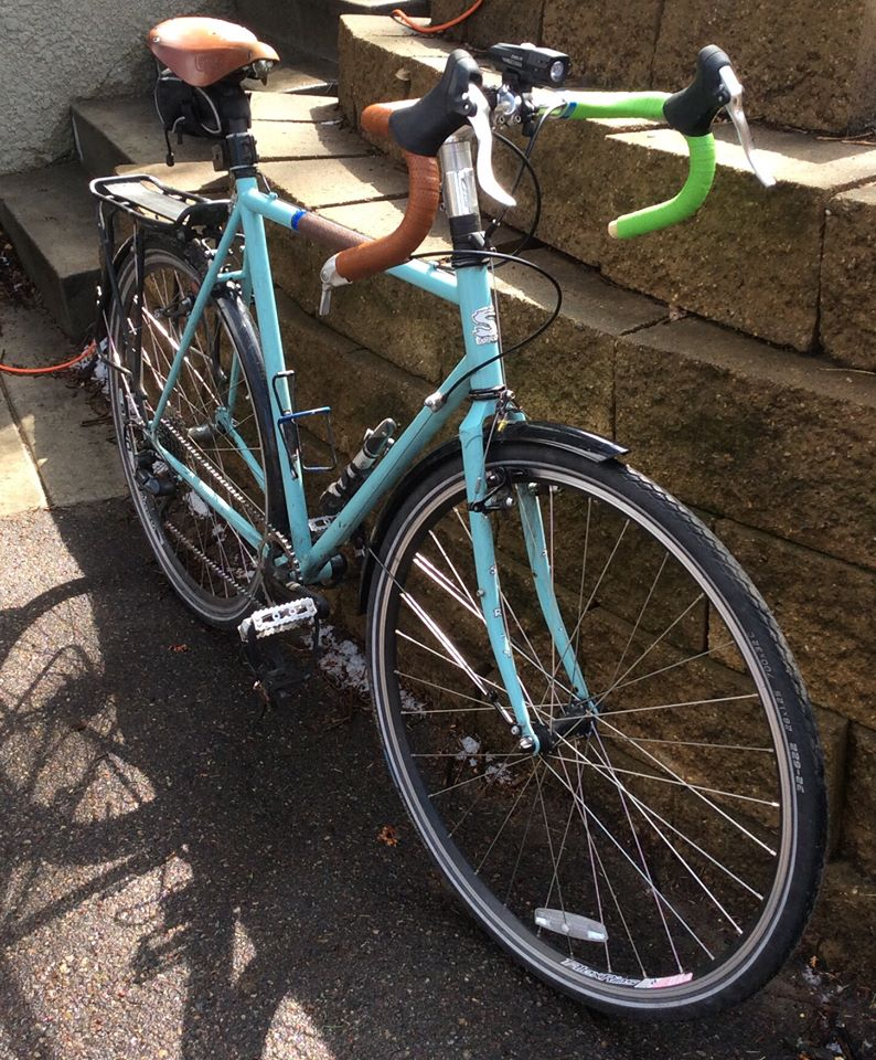 Front, right side view of a light blue Surly bike with fenders, parked against a wall constructed of landscape block