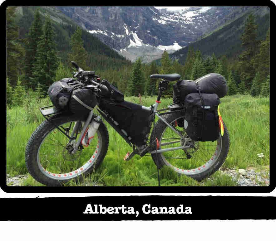 Left side view of a Surly fat bike, gray, on a field in the mountains - Alberta, Canada tag below image