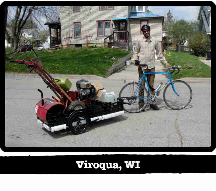 Cyclist standing on a street with a Surly bike, trailer with a soil tiller inside - Viroqua, WI tag below image