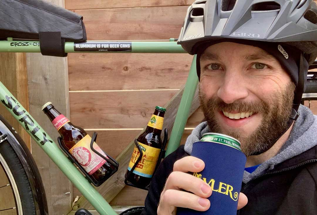 Close up of cyclist drinking a beer squatting down next to a green Surly bike with beer bottles in the bottles cages