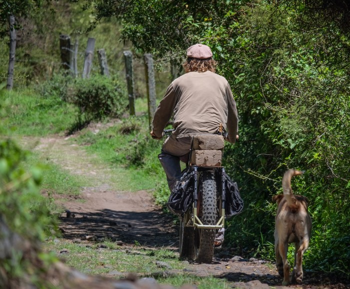 Rear view of a cyclist riding down a dirt trail alongside a fence, on a Surly Big Fat Dummy bike, with dog following