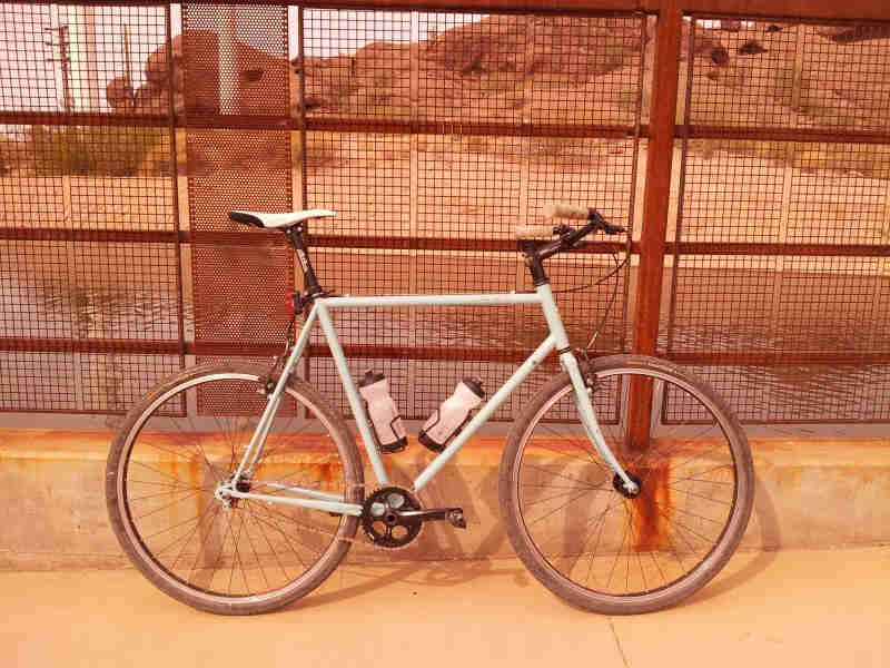 Right side view of a mint Surly bike, leaning against a steel grid fence, on a sidewalk, with water and hills behind it