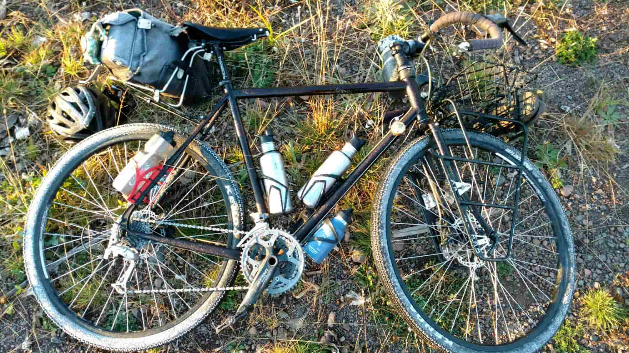 Downward left side view of a bike loaded with gear, laying on it's left side in gravel and weeds