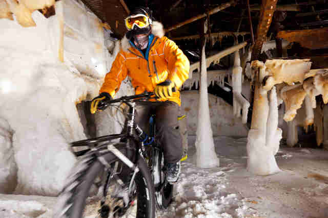 Front, left side view of a cyclist in winter outerwear, riding a Surly Moonlander fat bike in a steel structure on ice
