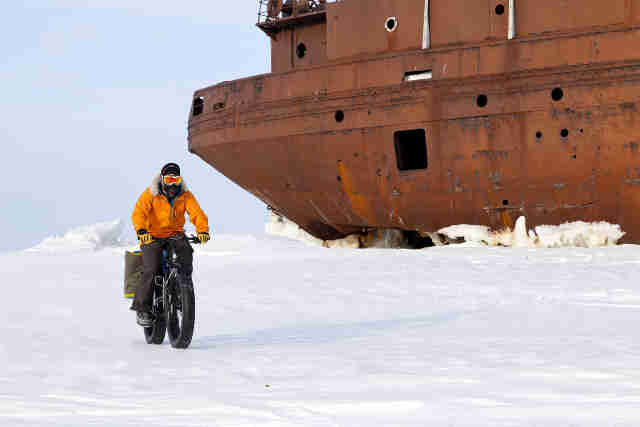 Front view of a cyclist in winter attire, riding a Surly Moonlander fat bike on a frozen field with grounded ship behind