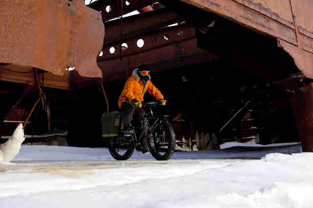 Front, right side view of a cyclist, wearing winter attire, riding a Surly Moonlander fat bike out of a structure on ice
