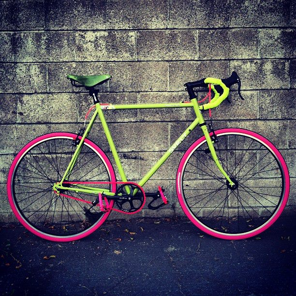 Right profile of a lime green Surly Cross Check bike with pink tires, leaning against a cinder block wall