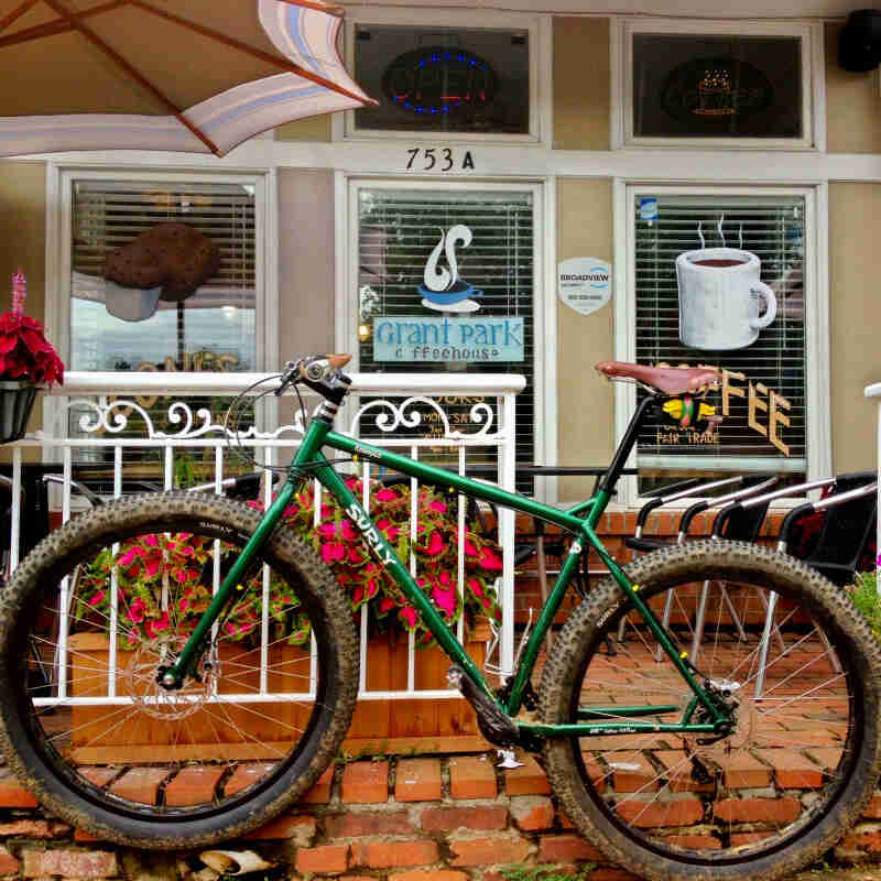 Left side view of a Surly Krampus bike, green, on a red brick sidewalk in front of a coffee shop