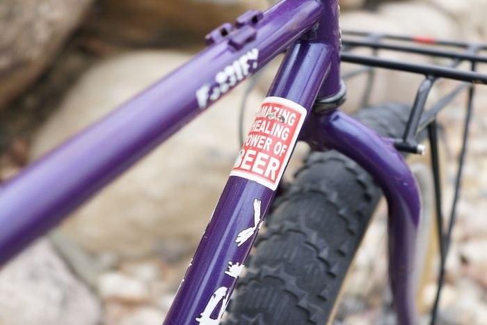 Close up partial view of the front of a purple Surly Pugsley fat bike top tube and down tube with white/red sticker