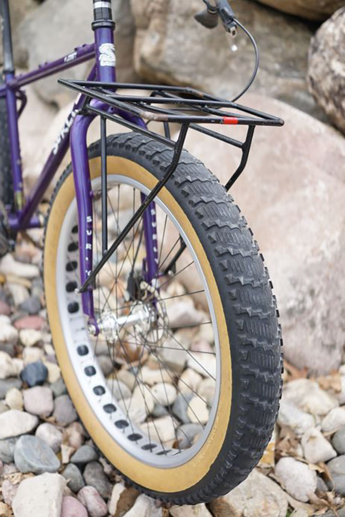 Front angle view of left side of purple Surly Pugsley fat bike with a fork carry rack, parked on rocks