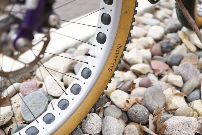 Downward angle view of 25 percent of a brake disc on a fat bike rim and tire with the word prototype sitting on rocks