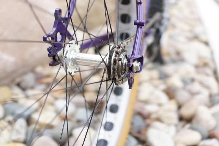 Close up of a fat bike wheel hub with free wheel sprocket and chain mounted to a purple Surly Pugsley fat bike