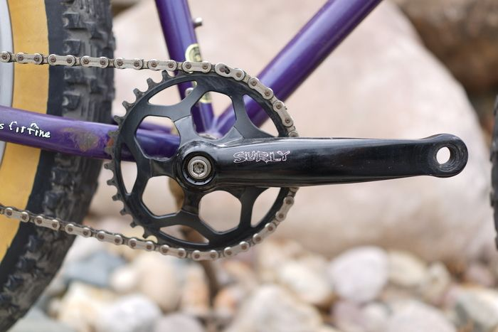 Close up of a black Surly crankset with a portion of the chain and rear tire on a purple Pugsley fat bike