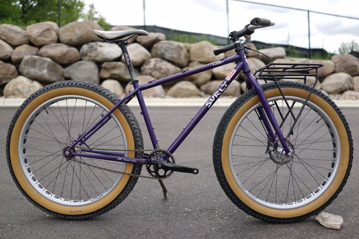 Left side view of a purple Surly Pugsley fat bike on pavement, with a boulder wall and chain link fence above it