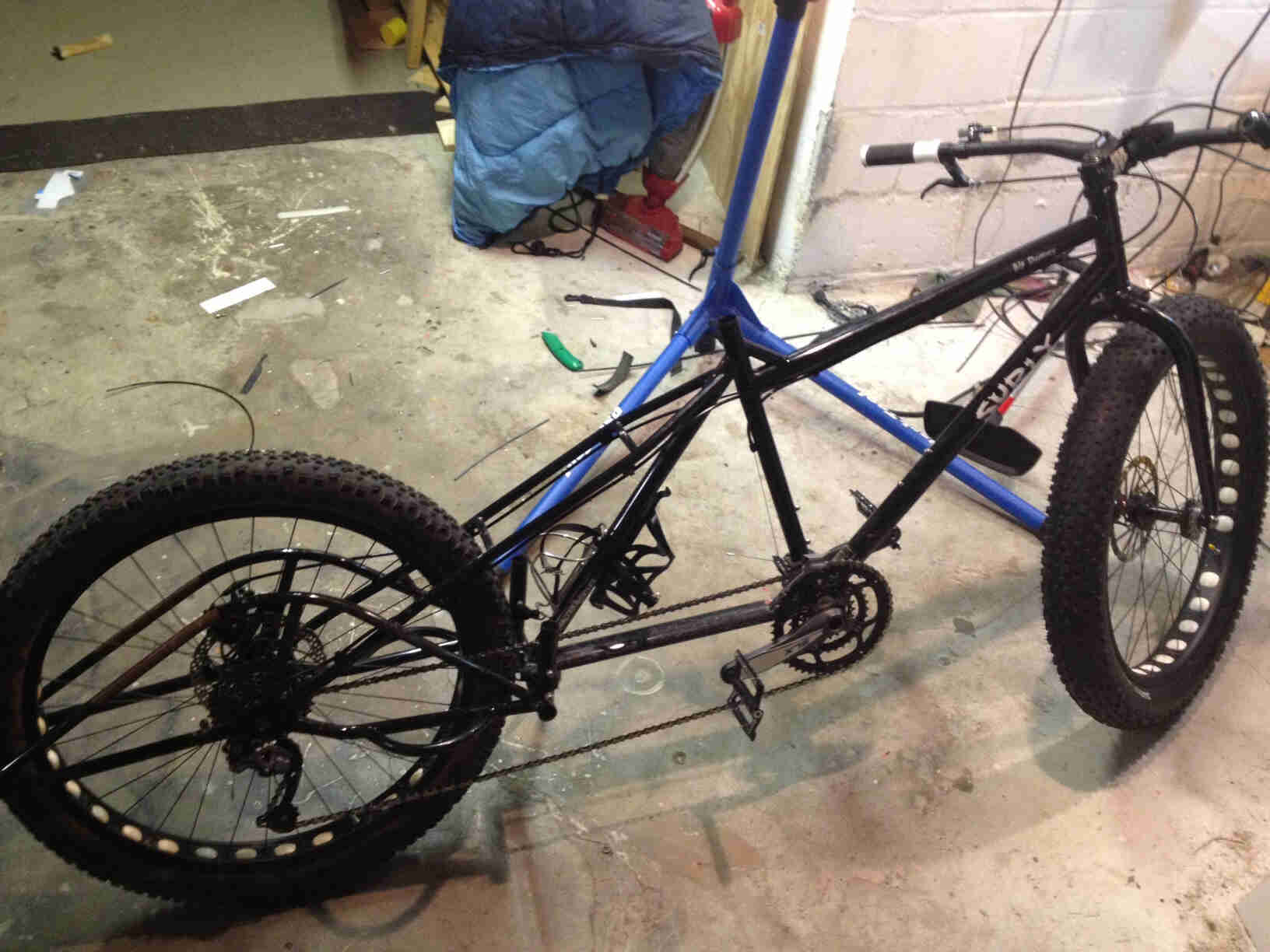 Right side view of a black Surly Big Dummy bike with a front fat wheel, without a seat or post, on a concrete floor