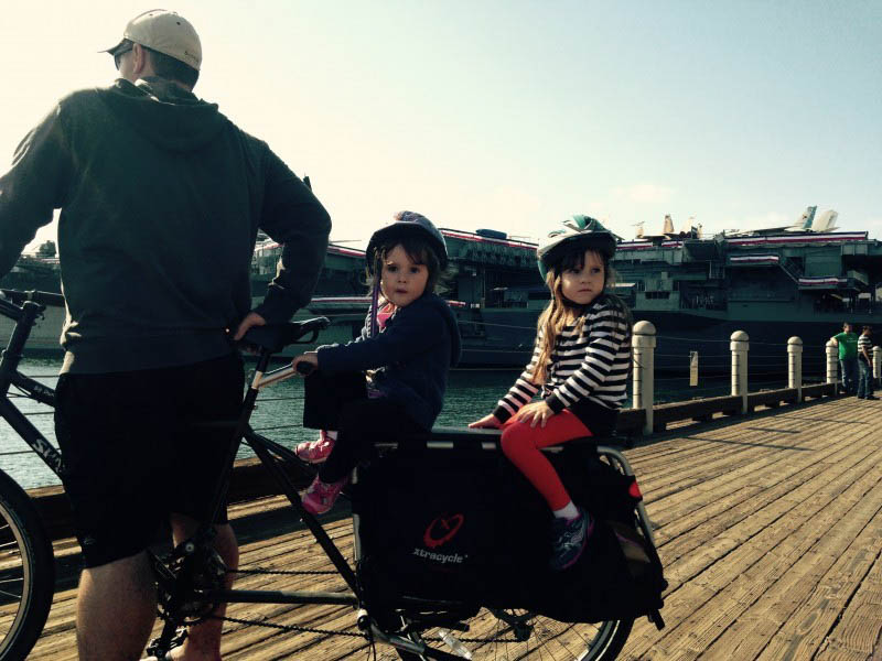 Right side view of a Surly Big Dummy bike with 2 children on back and a cyclist standing over, on a wood pier