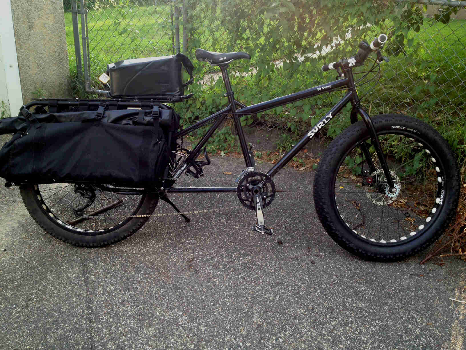 Right side view of a black Surly Big Dummy bike with a fat front wheel, on pavement, with a chain link fence behind