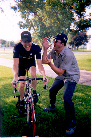 A person yelling in the ear of a cyclist riding a bike on grass