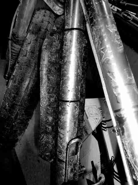 Close up, downward, left side view of a dirty fat bike - black & white image