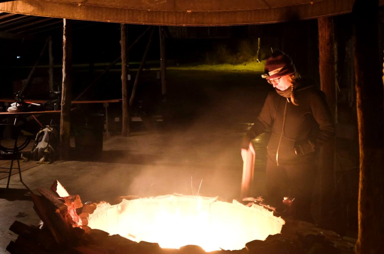 A person standing next to a campfire, under a park shelter, at night