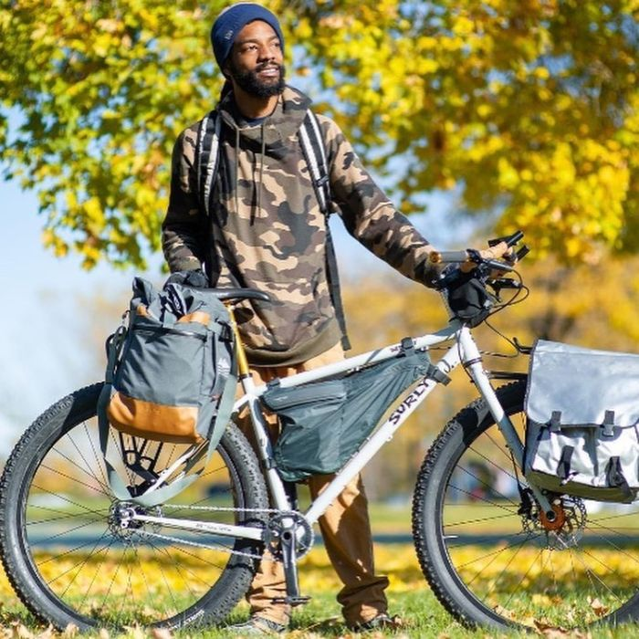 A cyclist wearing a camouflage sweatshirt stares off while holding a white Surly bike with gear attached