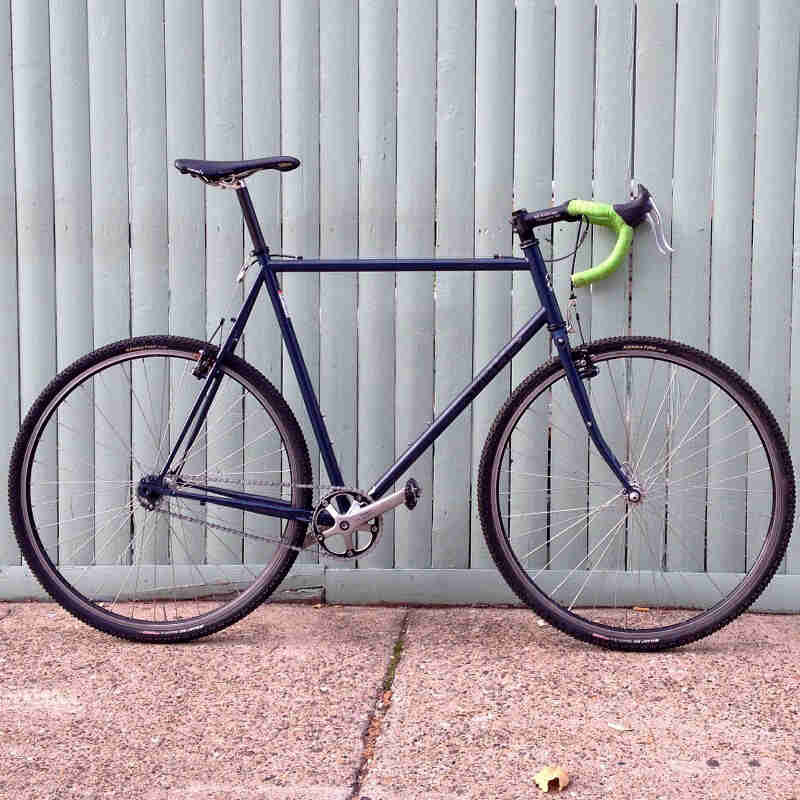 Right side view of a blue Surly Cross Check bike, parked on a sidewalk along a steel fence